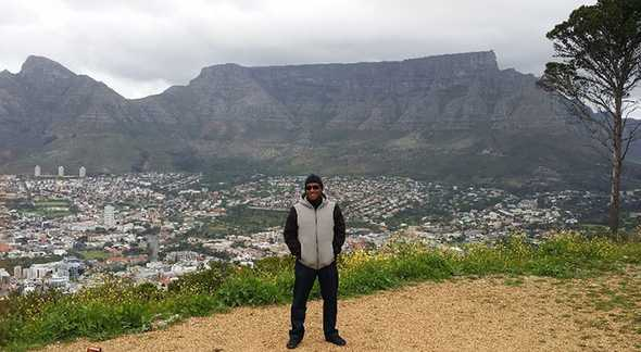 Adam standing on Signal Hill, with Table Mountain behind him. Photo by Waheed Adams.